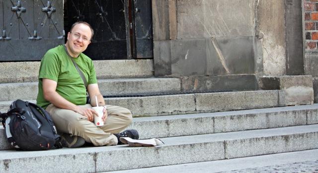 Autor siedzący na schodach z kapeluszem