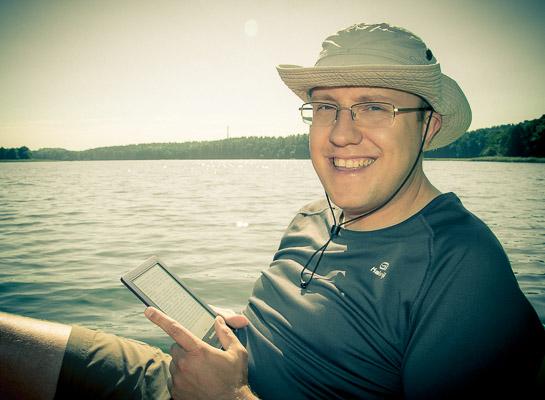 Autor z czytnikiem na jeziorze.
