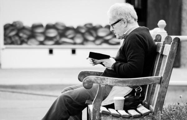 Starszy pan z czytnikiem i kawą